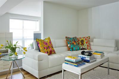 Sofá branco e almofadas florais e coloridas
