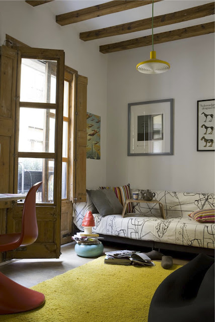 Sonniges Gelb bestimmt das Wohnzimmer: vintage ERCO-Leuchte und NANI MARQUINA Teppich aus recycelter Wolle