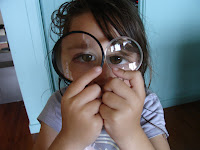 girl looking through magnifying glasses