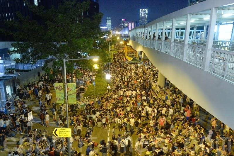 (上图)大批示威者27日晚上继续在政府总部外的添美道集会,学联宣布有6万人参与。