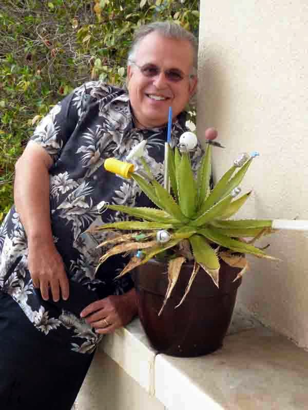 David Ocker in 2015 with his found-object-adorned plant but without his liquor collection