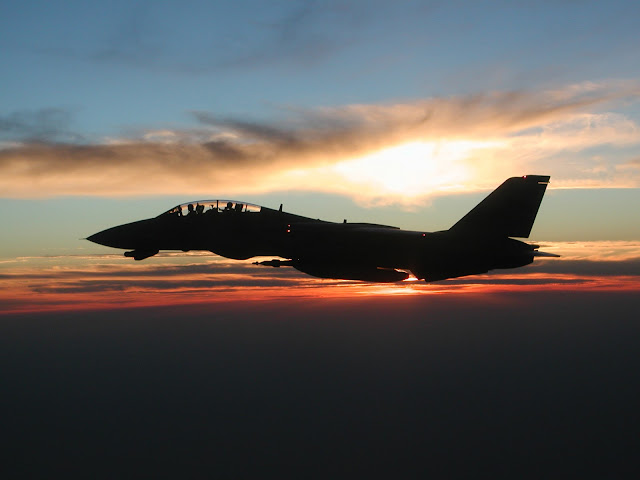 F-14D infligh with sunset behind it.