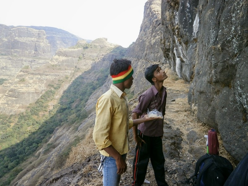 Kailash offering Puranpoli to the other local guide before doing a free climb of the 70 feet rock patch on Alang