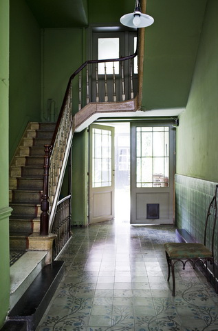 Green foyer with a staircase, tile floor, and white door