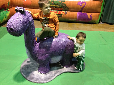 My kids riding the purple dinosaur.