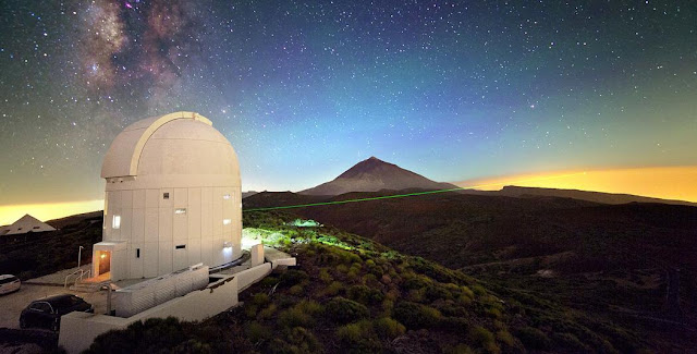 ESA's Optical Ground Station (OGS) is 2400 m above sea level on the volcanic island of Tenerife. Visible green laser beams are used for stabilising the sending and receiving telescopes on the two islands. The invisible infrared single photons used for quantum teleportation are sent from the neighbouring island La Palma and received by the 1 m Telescope located under the dome of the OGS. Initial experiments with entangled photons were performed in 2007, but teleportation of quantum states could only be achieved in 2012 by improving the performance of the set-up.  Aside from inter-island experiments for quantum communication and teleportation, the OGS is also used for standard laser communication with satellites, for observations of space debris or for finding new asteroids. The picture is a multiple exposure also including Tenerife's Teide volcano and the Milky Way in the background. Copyright IQOQI Vienna, Austrian Academy of Sciences