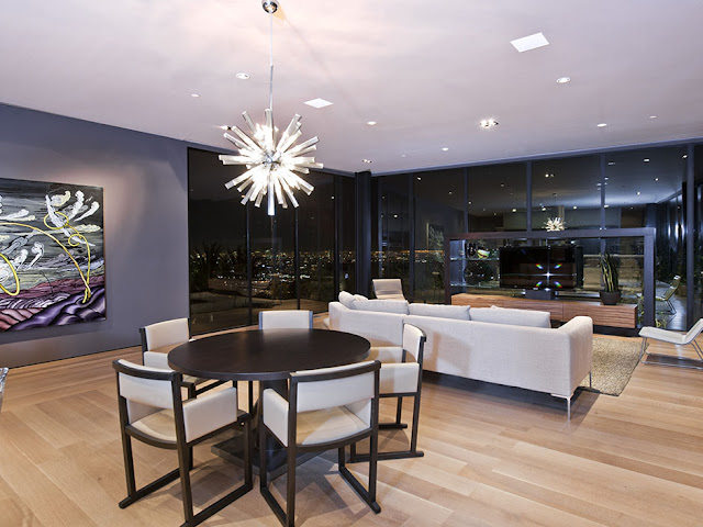 Photo of modern dining room and living room interiors at night with the city views through the windows