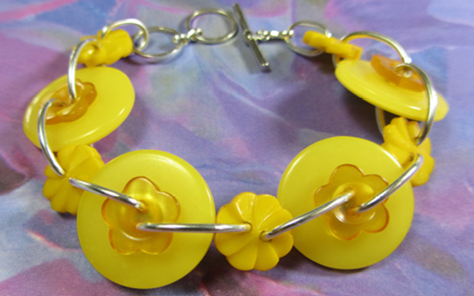 Yellow bracelet has cute big buttons and flower linked together