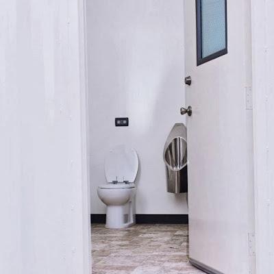 Foto de um vaso sanitário comum, dentro de um banheiro. Há um mictório de alumínio ao lado do vaso.