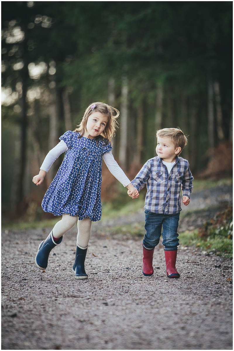 A young brother and sister skipping in the forest