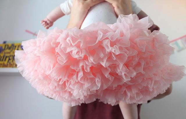 back of baby wearing big pink tutu being lifted into the air