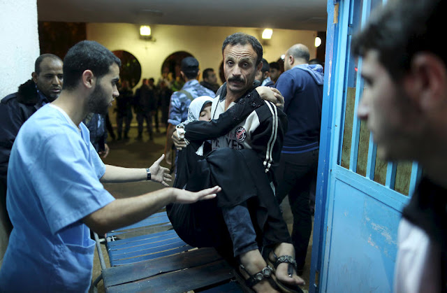 Palestino carrega sua filha, ferida por ataque aéreo israelense