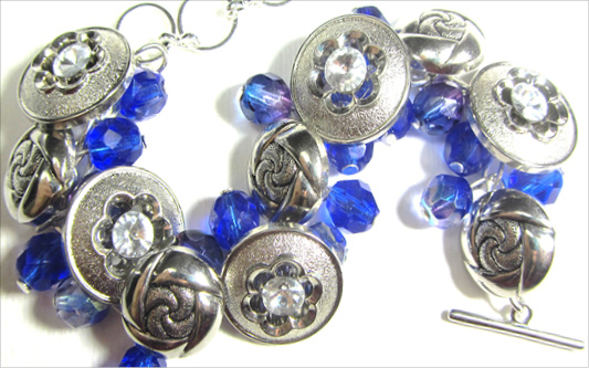 Bold bracelet has silver flower buttons with blue Fire Polished Czech Beads