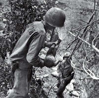 US. Marine cradles baby- the only survivor from hundreds dead Japanese in Siapan cave -summer of 1944