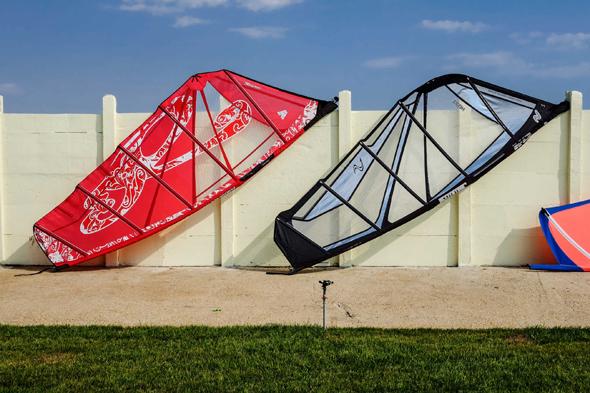 Fotografie di vele da windsurf appoggiate ad un muro