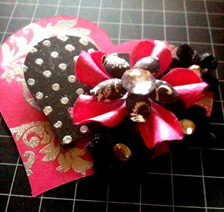 paper piecing heart made with plain pink card stock paper and embossed with silver. Second heart is black card stock embossed with silver polka dots and flowers added.