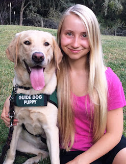 Hailey smiles with her arm around a yellow Lab guide dog puppy wearing the green puppy coat.