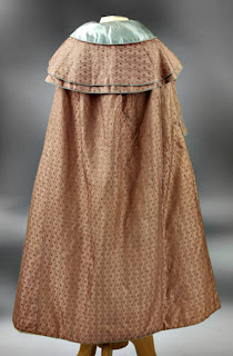 Cloak with capelets, arm slits and piped-bound edgings-back view