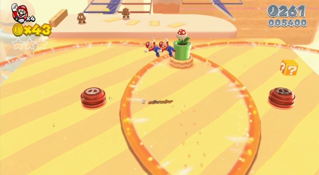 Two Marios jumping in colorful level of Super Mario 3D World with goombas walking around in the background