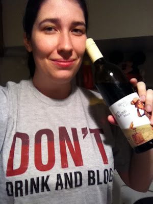 Jen wearing a shirt that reads 'Don't drink and blog' while holding a bottle of wine