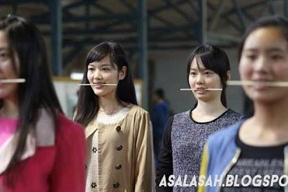 Remaja China Latihan senyum dengan Menggigit Sumpit