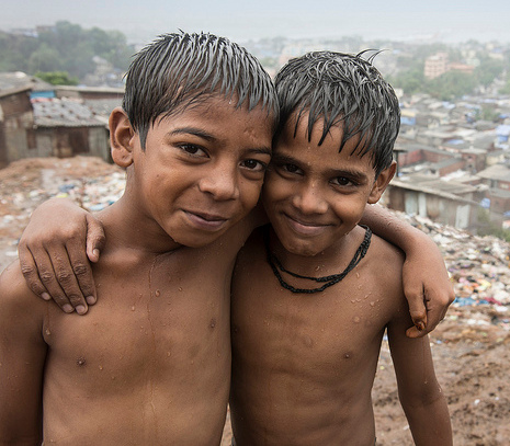 Two boys from Mumbai, India, with their arms around each other, smiling to the camera