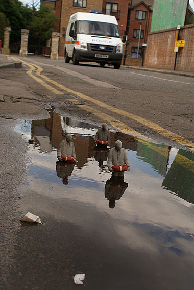 Street art. Three clay figures emerging from a puddle all wearing life-buoys. In the background a real British Police van.
