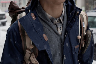 chico bajo la nieve con mochila