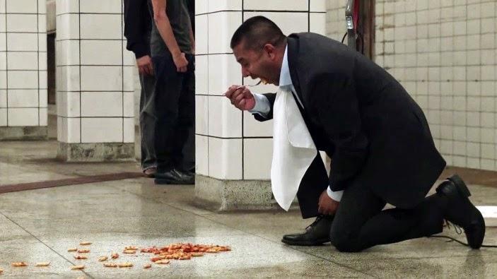رجل يأكل من أرضية رصيف مترو الأنفاق