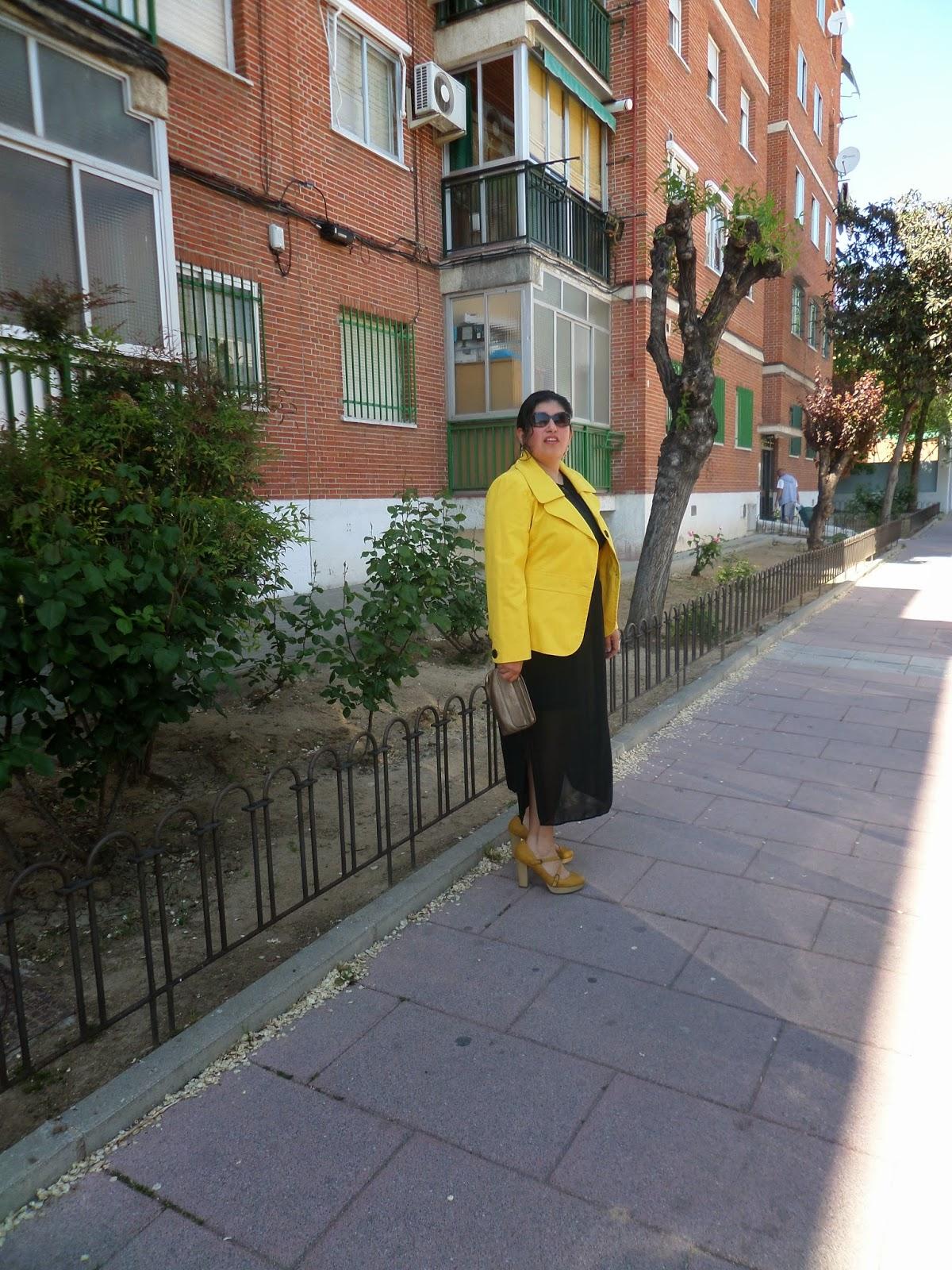 chaqueta amarilla y vestido negro con trasparencias