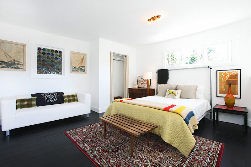 Bedroom in a cottage with stained wood floor, a red Moroccan rug, a white sofa with green plaid accent pillows and a navy throw with a seal on it, a bed with a metal headboard, a bench is at the foot of the bed and white walls