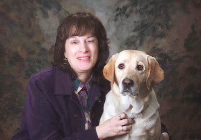 Roxanne (wearing a purple jacket) poses with Carnation (yellow Lab) in a studio portrait.