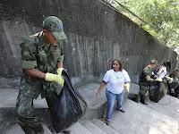 A Agente Comunitária de Saúde Rosane Landy e os fuzileiros navais formam a fila indiana para despachar o lixo coletado.