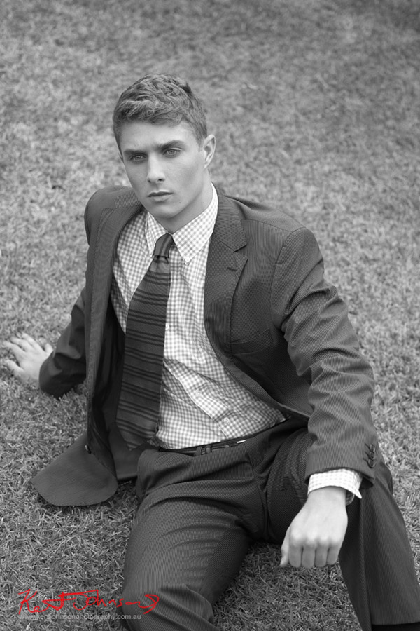 Semi reclining shot, seated wearing a business suit on the grass, male modelling.