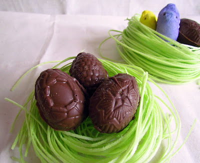 chocolate easter eggs on grass with PEEPS behind