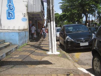 A calçada pública sofre com degraus, desníveis, sujeira, diferentes tipos de acabamento, postes mal planejados, além de ser estreita e espremida pelos automóveis. Falta ao centro da cidade um padrão de comunicação visual.