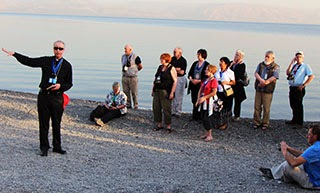 Pilgrims on the edge of Sea of Galilee at Tabgha