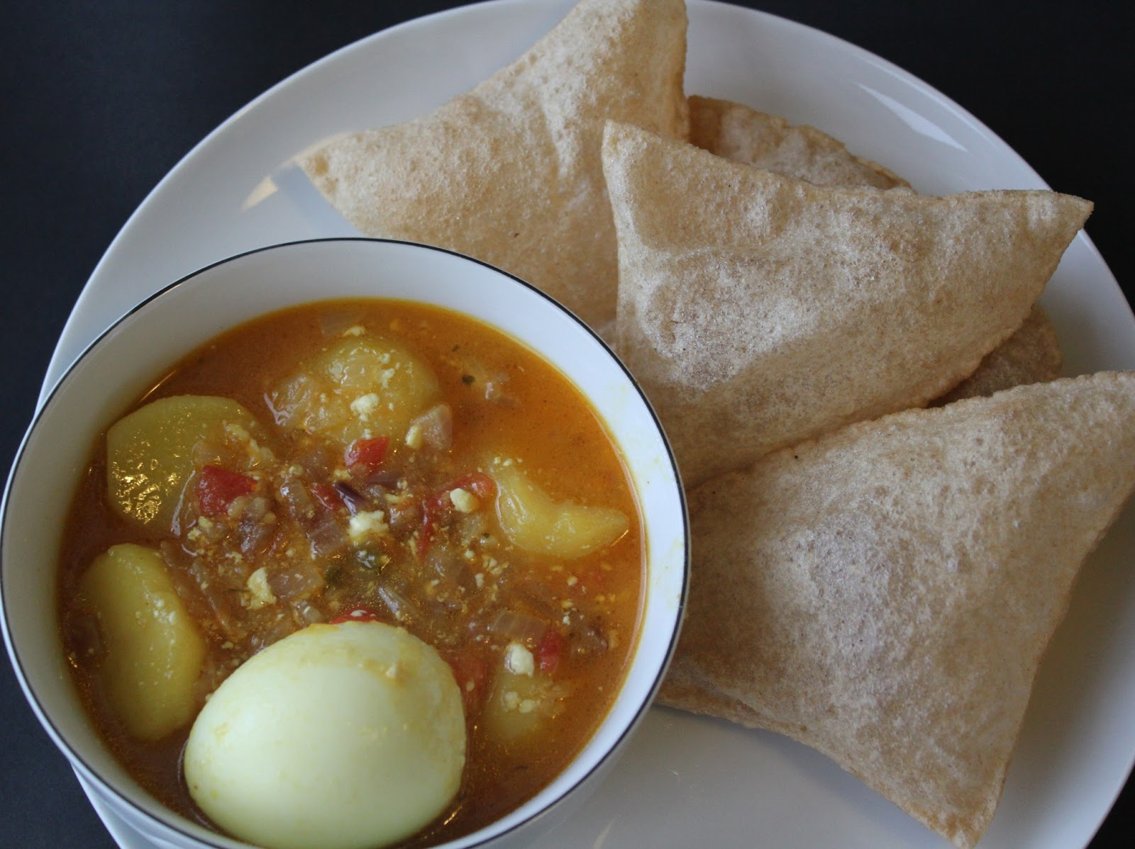 Lusi fried flat bread with mildly spiced egg curry for Assamese cuisine