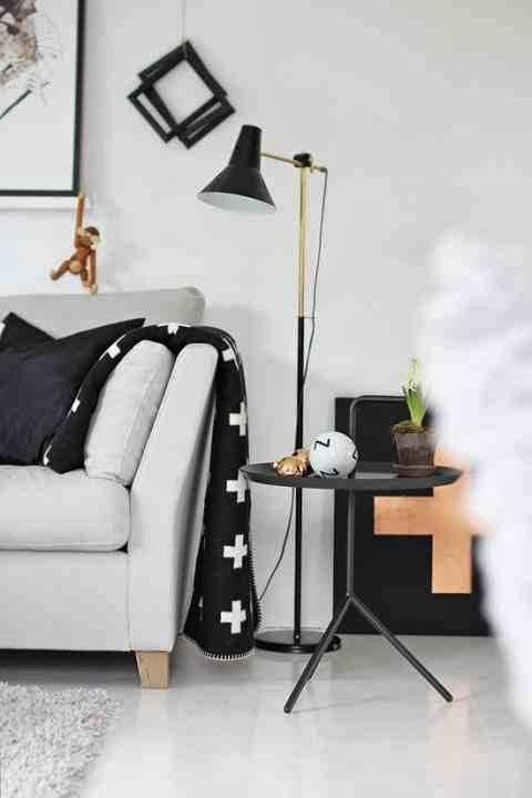 Aranżacja styl skandynawski, wnętrze skandynawskie, czarna, metalowa lampa stojąca, czarny stolik, biała sofa