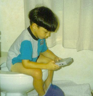 funny picture: child playing gameboy on toilet bowl