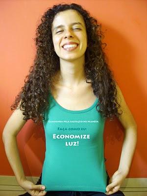Sara sorrindo, de olhos fechados, com camiseta verde com a seguinte estampa: Campanha pela salvação do planeta - Faça como eu: economize luz!