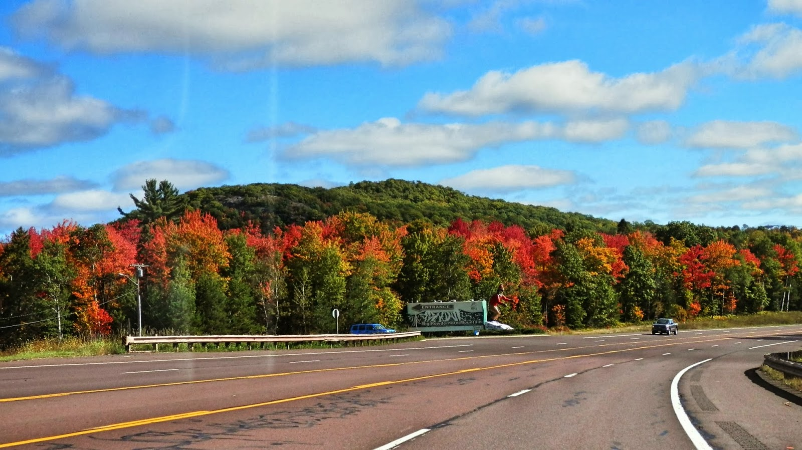 Taken through the car windshield, there are some trees starting to ...