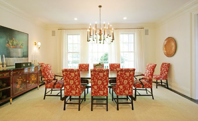 formal dining room with red upholstered chairs, an oval table, a chandelier, french doors with white curtains and traditional decor