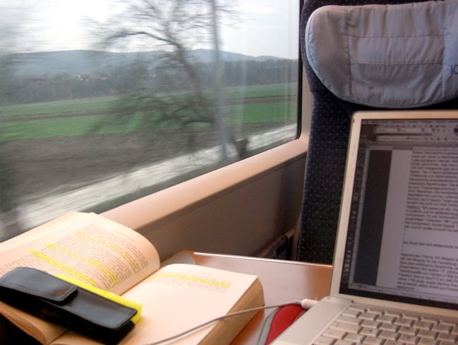 Zugfenster, vorbeisausende Landschaft, Laptop, Buch, Textmarker