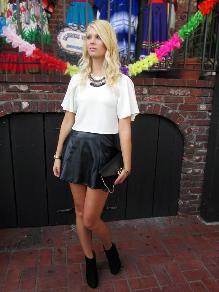 black leather skirt, white crop top, black wedge heels