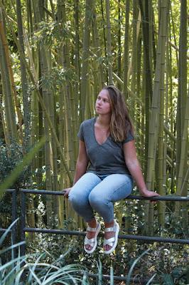Chica sentada en una valla con sandalias GEOX de Vives Shoes entre bambús.