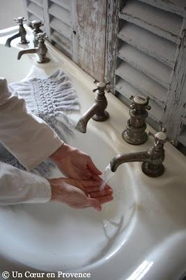 Vieux lavabo double sur pieds posé contre des persiennes chinés