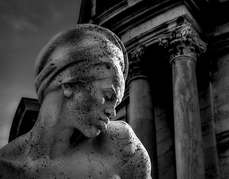 Pormenor da estátua com uma cabeça em primeiro plano e um edifício como fundo
