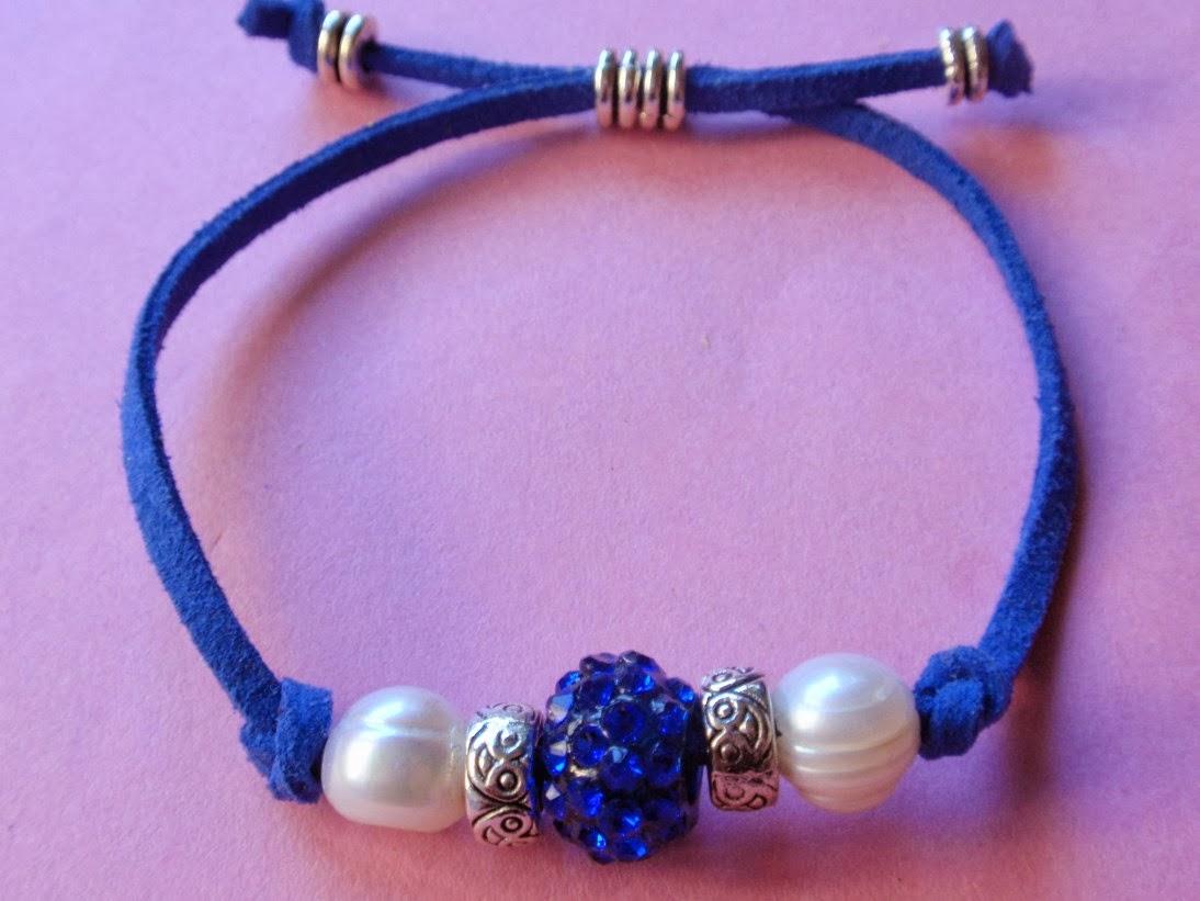 Pulsera ajustable en antelina color azul con cristal del mismo color en el centro y perlas de agua dulce a los lados.