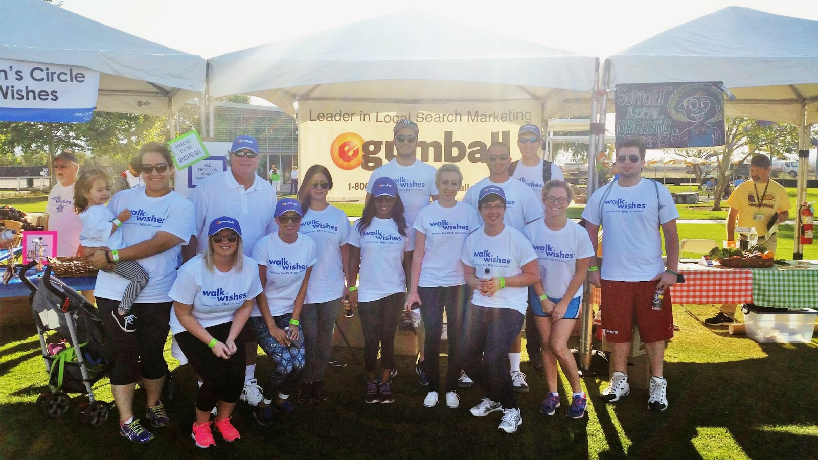 Employees from eGumball, Inc. posing for a photograph in front of their booth at the Make-A-Wish Foundation's Walk for Wishes event.
